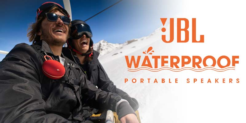 Smiling couple on a ski lift. The guy is weating a JBL Clip 3 water proofspeaker on his jacket