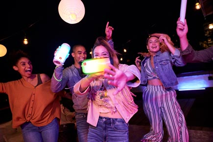 Friends walking in a group with 2 glowing JBL Pulse 4 speakers