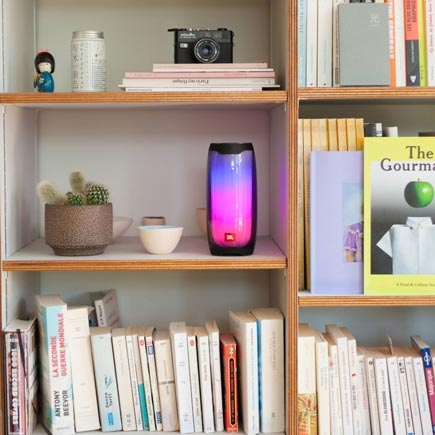 Glowing JBL Pulse 4 speaker in a bookcase